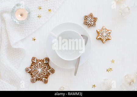 Christmas background. Empty white cup, gingerbread, candles and knitted scarf on a white wooden background. Light still life. Flat lay, top view, copy