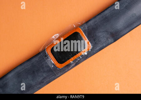 Patch on the camera of the bike. bicycle repair kit, wheels camera on wooden background - Stock Photo