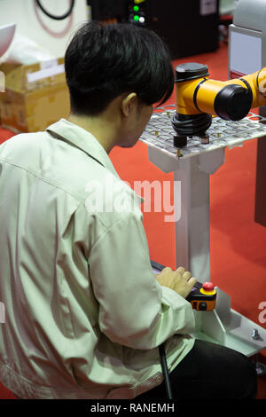 Worker control robot arm to loading and unloading workpiece - Stock Photo