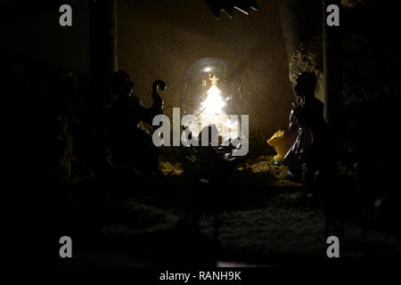 Nativity Scene in silhouette.Silhouette of the Nativity Scene with statues of Joseph, Mary and the little Jesus inside the hut. - Stock Photo