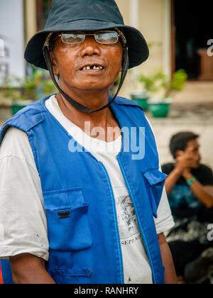 Adult Indonesian male in blu jacket on street of Jakarta - Stock Photo