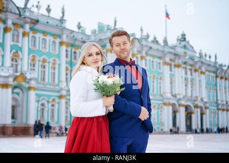 beautiful woman in red dress and man posing standing in winter, wedding in St. Petersburg. - Stock Photo