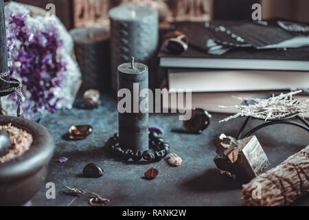 Black candle on a witch's altar for a magical ceremony among