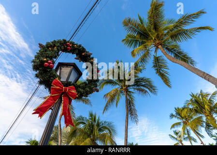 Christmas decorations with a red ribbon on a public lamp post with tropical palms in the background. Key West, Florida. - Stock Photo