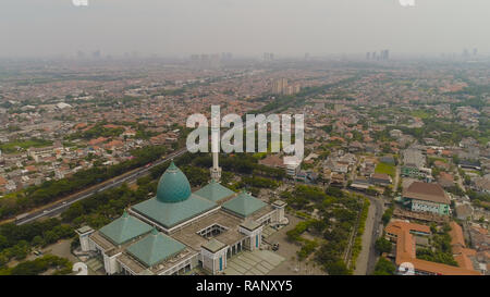aerial view cityscape city Surabaya with mosque Al Akbar, highway, skyscrapers, buildings and houses. mosque in Indonesia Al Akbar in Surabaya, Indonesia. beautiful mosque with minarets on island Java Indonesia. - Stock Photo
