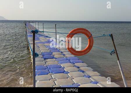 Closed with red lifebuoy and ropes passage to swimming area on summer tropical beach. Horizontal color photography. - Stock Photo