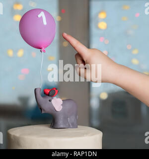 Child's hand pointed outThe concept of a children's holiday. Confectionery advertisment background. - Stock Photo