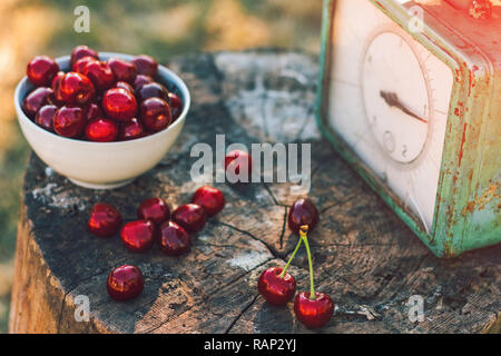 Tasty sweet cherry in a bowl on a wooden stump with old weights - Stock Photo