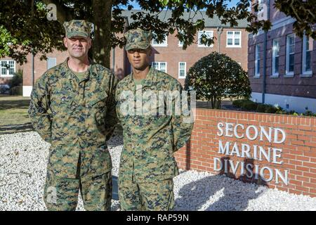U.S. Marine Corps Sgt. Maj. Michael P. Woods, sergeant major, 2nd Marine Division (2d MARDIV), stands with Cpl. Demarcus R. Robinson, 2d MARDIV, following a morning colors ceremony on Camp Lejeune, N.C., Feb. 22, 2017. During this ceremony Maj. Gen. John K. Love, commanding general, 2d MARDIV, recognized Marines and Sailors, within the 2d MARDIV, who set themselves apart from their peers during the previous quarter by demonstrating their leadership abilities, espirit de corps and their skill and will. - Stock Photo