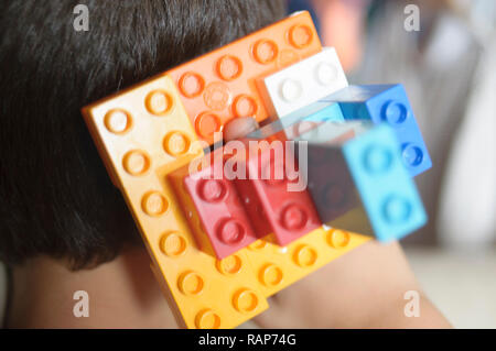 Boy playing with lego construction toy blocks. - Stock Photo