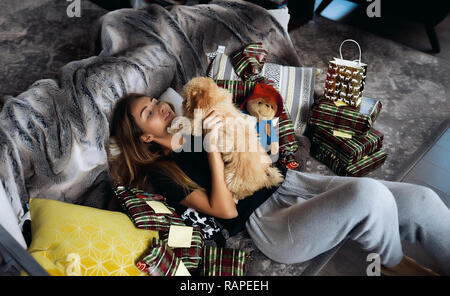 Winter picture of pretty blonde woman in black shirt and grey pants. Lying on a couch with little cute puppy in hands. A lot of presents around - Stock Photo