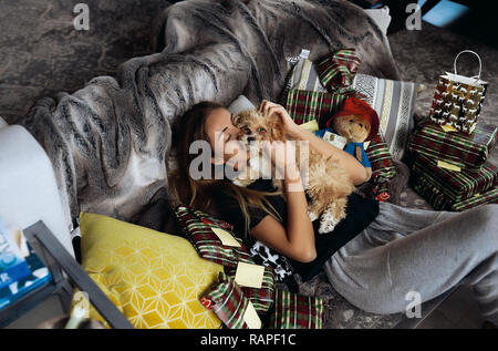 Tender young blonde lying on a couch, kissing and hugging her puppy. Tender and warm relations, love and care. Christmas presents from relatives. - Stock Photo