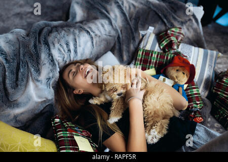 Funny young woman having fun with little puppy on a sofa. Spend together winter holidays, a lot of presents around. Tender skin, beautiful face. - Stock Photo