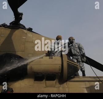 Spc. Christian Aquino and Pfc. Kurtis Carson of the 355th CBRN company from Sloan, Nevada power-spray the engine of a CH-47 Chinook helicoper during detail decontaminatin training near Erbil, Kurdistan, Iraq on March 1, 2017. This training is part of the overall Combined Joint Task Force – Operation Inherent Resolve building partner capacity by training and improving the capability of partnered forces fighting ISIS. CJTF-OIR is the global Coalition to defeat ISIS in Iraq and Syria. - Stock Photo