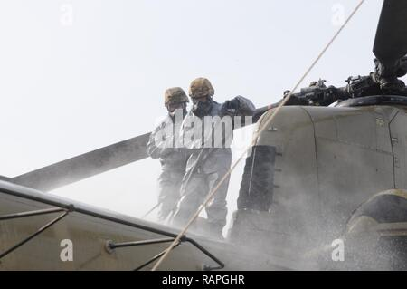 Spc. Christian Aquino and Pfc. Kurtis Carson of the 355th CBRN company from Sloan, Nevada power-spray the roof of a CH-47 Chinook helicoper during detail decontaminatin training near Erbil, Kurdistan, Iraq on March 1, 2017. This training is part of the overall Combined Joint Task Force – Operation Inherent Resolve building partner capacity by training and improving the capability of partnered forces fighting ISIS. CJTF-OIR is the global Coalition to defeat ISIS in Iraq and Syria. - Stock Photo