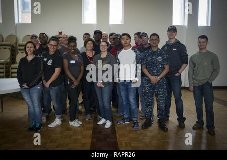 NORFOLK (Feb. 27, 2017) Volunteers pose for a group photo after a volunteer effort at the Ohef Sholom Temple Soup Kitchen. Sailors assigned to the aircraft carrier USS George Washington (CVN 73), the amphibious assault ship USS Wasp (LHD 1) and Assault Craft Unit (ACU) 2 from Naval Beach Group (NBG) 2 joined members of the Ohef Sholom Temple in preparing food and distributing donated goods to those in need during the temple's monthly soup kitchen in Norfolk. - Stock Photo