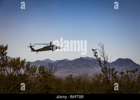 An HH-60G Pave Hawk descends to land in support of a U.S. Air Force and Marine joint exercise as part of a simulated Tactical Recovery of Aircraft and Personnel scenario, Feb 22, 2017, at the Playas Training and Research Center, N.M. During the scenario, Marines from I Marine Expeditionary Force from Marine Corps Base Camp Pendleton, Calif., rescued isolated personnel from a downed aircraft while fending off mock opposition forces from Davis-Monthan Air Force Base, Ariz.'s 563d Operations Support Squadron. This joint effort prepared the IMEF by completing their Special Purpose Marine Air Groun - Stock Photo
