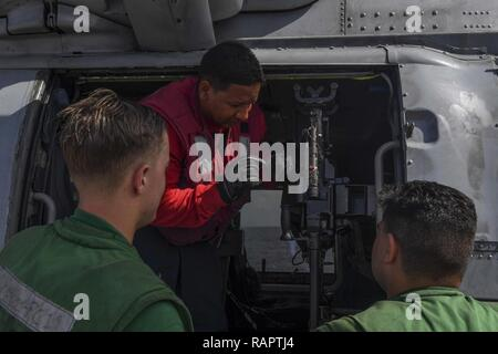 SOUTH CHINA SEA (Feb. 20, 2017) Aviation Ordnanceman 1st Class Nicholas Gravesande, from Brooklyn, New York, teaches Sailors about the M240 gun attached to an MH-60R Sea Hawk helicopter, attached to Helicopter Maritime Strike Squadron (HSM) 78, after it landed on the flight deck of Arleigh Burke-class guided-missile destroyer USS Wayne E. Meyer (DDG 108) to prepare for a replenishment-at-sea with Henry J. Kaiser-class underway replenishment oiler USNS Tippecanoe (T-AO 199). Wayne E. Meyer is on a regularly scheduled Western Pacific deployment with the Carl Vinson Carrier Strike Group as part o - Stock Photo