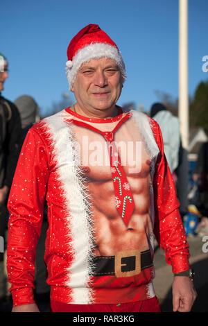 Man in fancy dress at the New Year's Day swim at Rhu Marina, Argyll, Scotland. - Stock Photo