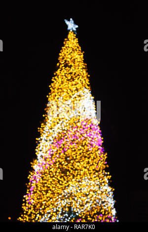 Glittering Glowing Sparkling Gold defocused Night Light (bokeh) Illumination background with decorated Christmas Tree. Special Holidays, Festival desi - Stock Photo