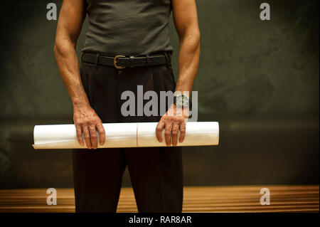 Man in sleeveless top stands holding a long roll of papers. - Stock Photo