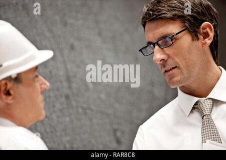 Businessman in a hardhat talks with a male colleague wearing eyeglasses. - Stock Photo