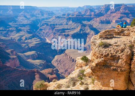 hiker couple sitting at edge of Grand Canyon enjoying the views - Stock Photo