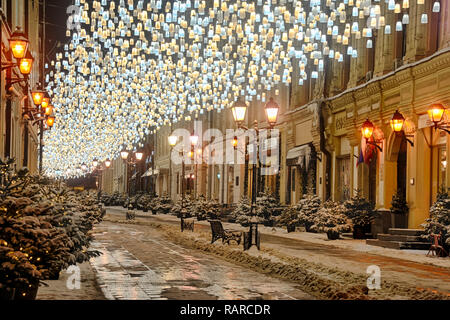 = Festive Lights and Christmas Trees at Stoleshnikov Lane in Early Morning =  Beautiful Christmas decorations light up Stoleshnikov lane, one of the m - Stock Photo