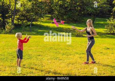 Mother and son playing with a large model toy aeroplane in the park