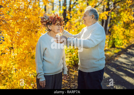 Happy old couple having fun at autumn park. Elderly man wearing a wreath of autumn leaves to his elderly wife - Stock Photo