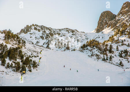 Tourists and locals running down in a snow slope in Andorra in Europe - Stock Photo