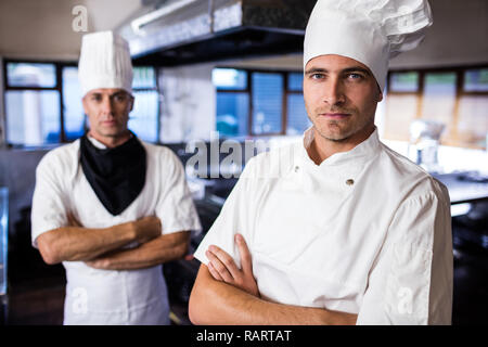 Two male chefs standing with arms crossed in kitchen - Stock Photo