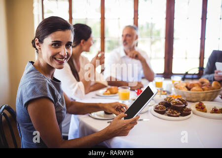 Businesswoman looking at camera while using digital tablet