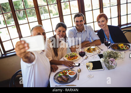 Business people taking selfie with mobile phone - Stock Photo