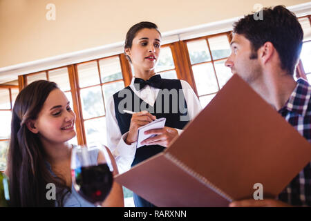 Waitress taking an order from a couple - Stock Photo