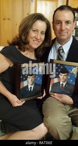 Roxann Burns and retired Chief Master Sgt. Bryan Burns, 60th Operations Support Squadron, pose for a photo in their home Feb. 7, 2017, while holding photographs of their sons after they completed Air Force basic training. Roxann is holding a photo of Joshua Burns and Bryan is holding a photo of Matthew Burns. Matthew is currently an Air Force staff sergeant assigned to the 79th Air Refueling Squadron at Travis Air Force Base, Calif., and Joshua left the Air Force after nearly nine years of service, all at Travis AFB. - Stock Photo