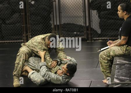 Sgt. Aaron Cochran, a culinary specialist with 3rd Special Forces Group (Airborne), fights Spc. Ricardo Rodriguez, a motor transport operator with 18th Fires Brigade (Airborne), during a Modern Army Combatives Class at the XVIII Airborne Corps and Fort Bragg Combatives School N.C., Feb. 10, 2017. The warriors of the class endured 5 days and 40 hours of training as an introduction to Modern Army Combatives. - Stock Photo