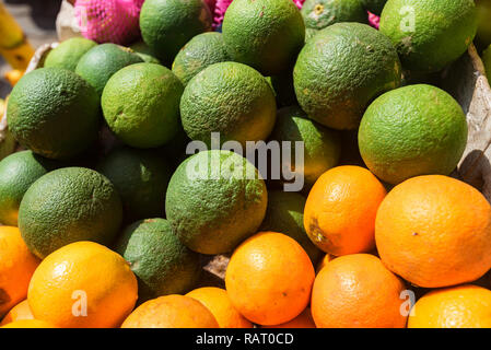 Limes and oranges in pile. Close up, selective fcus - Stock Photo