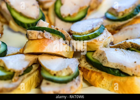 Appetizer sandwiches with meat and cucumber on plate close - Stock Photo