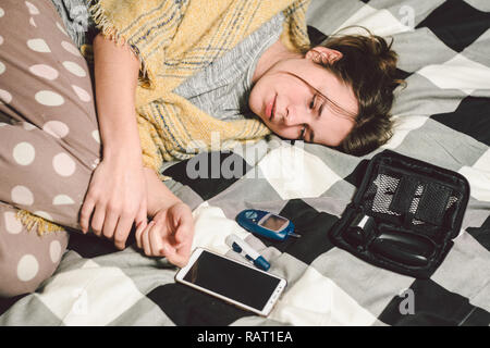 Theme diabetes. young caucasian woman at home in the bedroom on the bed uses the technology of the device for measuring blood glucose, glucometer test - Stock Photo