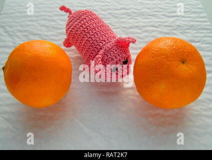 Chinese new year, toy bound pig-a symbol of wealth, next to the tangerines. - Stock Photo