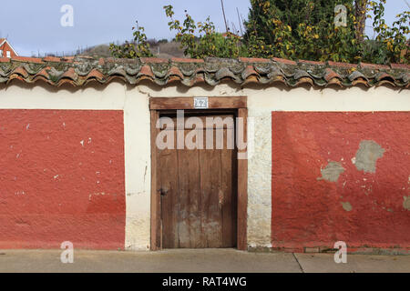 Rustic wooden door entrance to a field with trees in the background in a small village of Leon, Spain. - Stock Photo