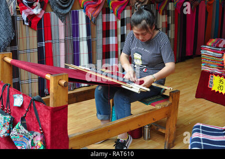 Young Chinese woman working on a loom weaving a red scarf - Stock Photo