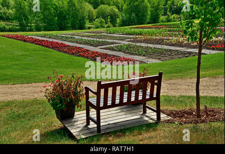 A horizontal landscape image with an empty bench seat overlooking an area thats planted with flowers in the Devonian Gardens near Edmonton Alberta. - Stock Photo