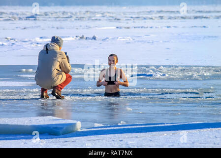 Dnipro city, Ukraine 19 01 2017. Winter sport. Beautiful girl swims swims in the winter river covered with ice during the Orthodox holiday of Epiphany - Stock Photo