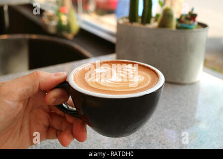 A man's hand holding a cup of cappuccino coffee with unique latte art, blurry table in background - Stock Photo