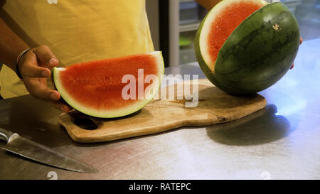 male hand with knife cuts watermelon. watermelon on cutting board. - Stock Photo