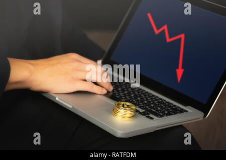 Businessman working on laptop with a golden bitcoin coins stack on it. Red chart, price crash concept. - Stock Photo