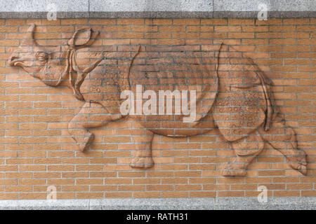 Rhinoceros emerges in red brick - Stock Photo