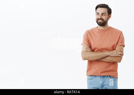 Father looking at son playing on playground feeling proud and happy. Charming adult bearded male with black hair crossing arms on chest in confident and self-assured gesture smiling gazing left - Stock Photo